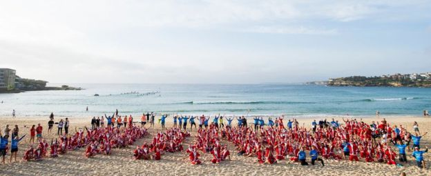 Hundreds of Santas learn to surf